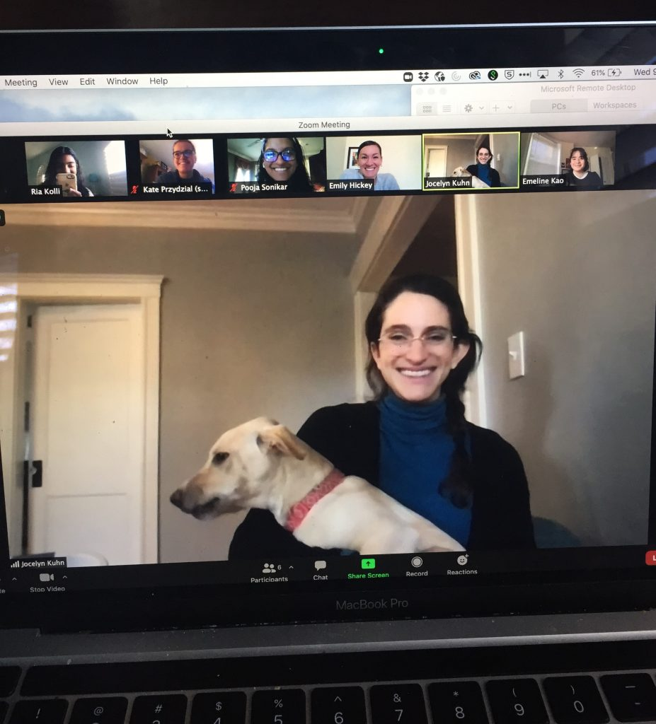 On a zoom call, one participant is holding a dog and smiling. All other participants are laughing and smiling at the dog.
