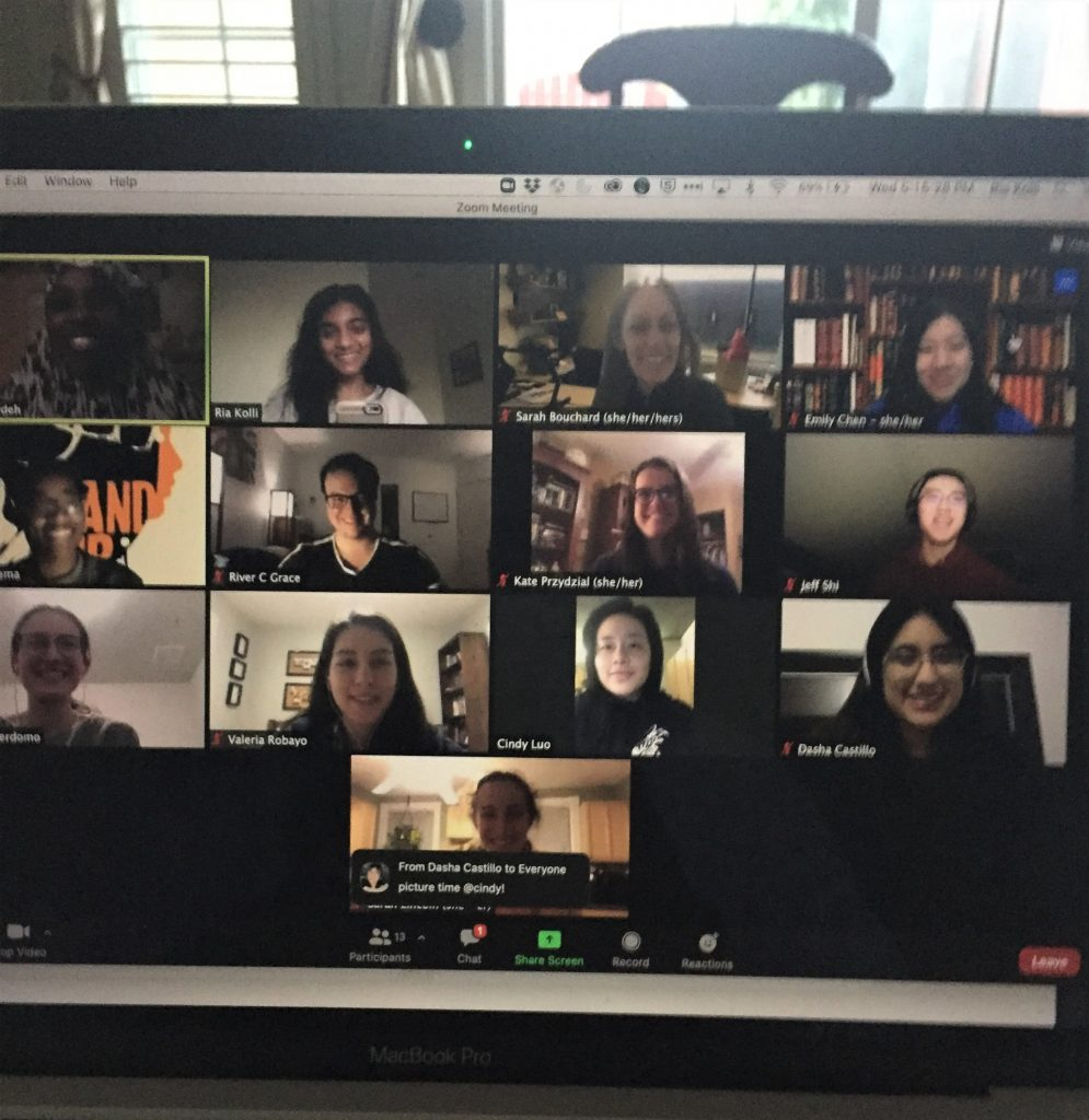 "A photo of a laptop screen showing a zoom call with 13 people. A chat message reads ""picture time @cindy!"" and all the participants are smiling for the photo."