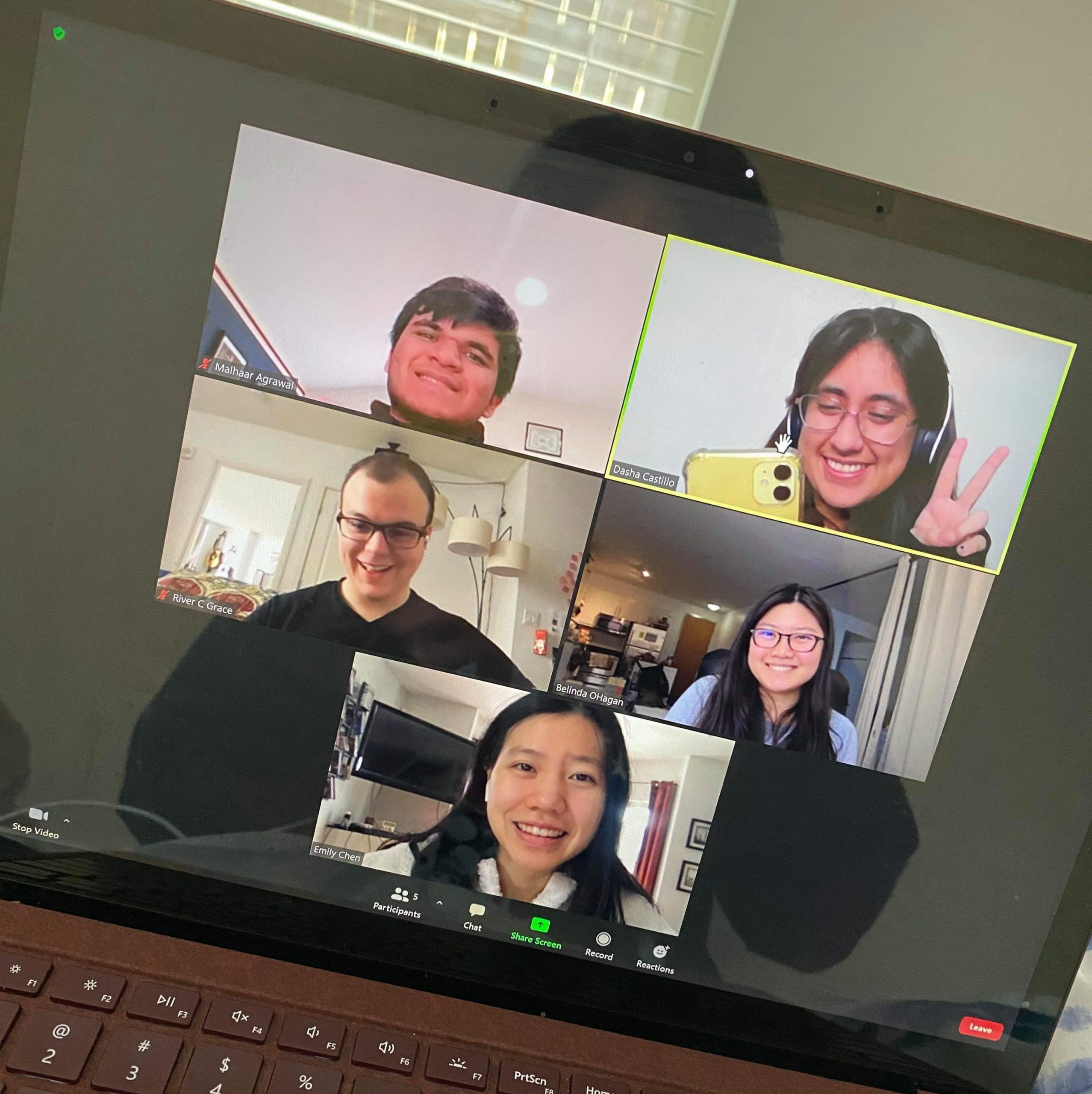 A photo of a laptop screen picturing a zoom call with 5 people, all posing for the photo.